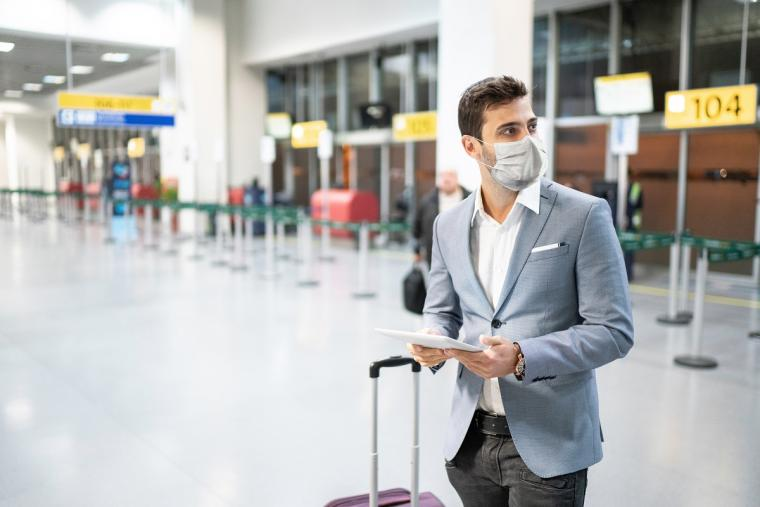 Man%20wearing%20mask%20at%20airport%20and%20checking%20in%20with%20tablet%20